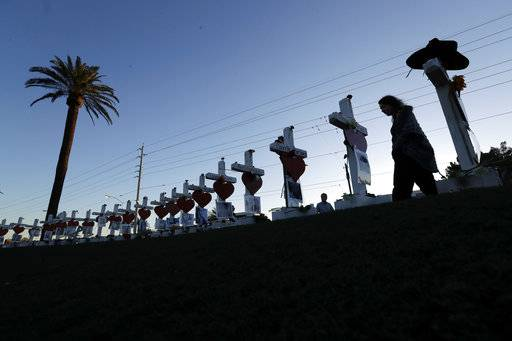 Manuela Barela passes crosses set up to honor those killed during the mass shooting Friday, Oct. 6, 2017, in Las Vegas. A gunman, Stephen Paddock, opened fire on an outdoor music concert on Sunday killing dozens and injuring hundreds.