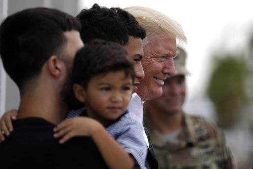 President Donald Trump poses for a photo as he visits a disaster relief distribution center at Calgary Chapel in Guaynabo, Puerto Rico, Tuesday, Oct. 3, 2017. Trump is visiting Puerto Rico in the wake of Hurricane Maria.