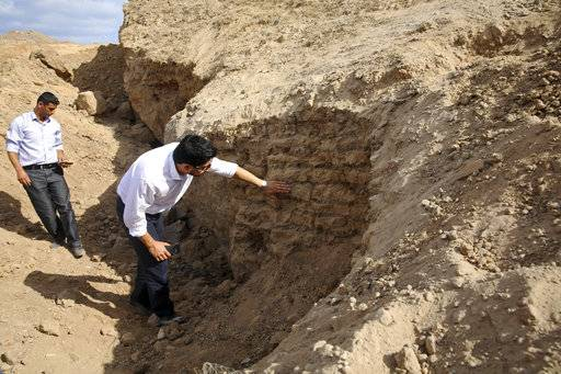 In this Tuesday, Sept. 26, 2017 photo, Junaid Sorosh-Wali, a UNESCO official, inspects damage at Tel Es-Sakan hill site, south of Gaza City. Palestinian and French archaeologists began excavating Gaza's earliest archaeological site nearly 20 years ago; unearthing what they believe is a rare 4,500-year-old Bronze Age settlement. But over protests that grew recently, Gaza's Hamas rulers have systematically destroyed the work since seizing power a decade ago, to make way for construction projects, and later military bases.