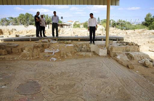 In this Tuesday, Sept. 26, 2017 photo, Junaid Sorosh-Wali, right, a UNESCO official, inspects the remains of a mosaic at St. Hilarion monastery, a site of early Christianity, in Nusseirat, central Gaza Strip. Gaza is home to numerous ancient treasures, but politics have long complicated archaeological work. At the monastery, which spans from the late Roman Empire to the Islamic Umayyad period, a breach in the fence suggested looters were trying to get in.