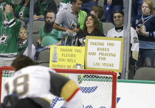 A fan holds a sign in the stands during warm ups before an NHL hockey game between the Vegas Golden Knights and Dallas Stars in Dallas, Friday, Oct. 6, 2017.