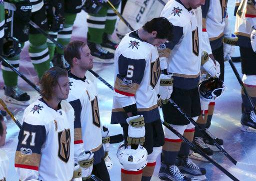 Vegas Golden Knights defenseman Colin Miller (6) bows his head as he lines up with teammates and the Dallas Stars for a moment of silence for shooting victims in Las Vegas before an NHL hockey game in Dallas, Friday, Oct. 6, 2017.