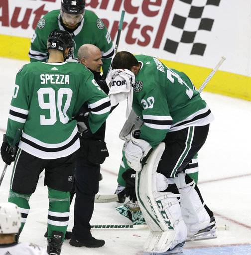 Dallas Stars goalie Ben Bishop (30) is tended to after getting hit by the puck on the face, as teammates Jason Spezza (90) and Stephen Johns (28) watch during the third period of an NHL hockey game against the Vegas Golden Knights in Dallas, Friday, Oct. 6, 2017. The Golden Knights won 2-1.