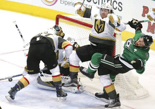 Dallas Stars center Tyler Seguin (91) is hit by Vegas Golden Knights James Neal (18) as teammates Luca Sbisa (47) and goalie Marc-Andre Fleury cover the goal during the second period of an NHL hockey game in Dallas, Friday, Oct. 6, 2017.