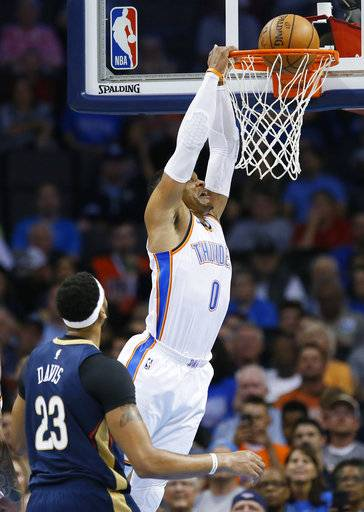Oklahoma City Thunder guard Russell Westbrook dunks in front of New Orleans Pelicans forward Anthony Davis during the first quarter of an NBA preseason basketball game in Oklahoma City, Friday, Oct. 6, 2017.