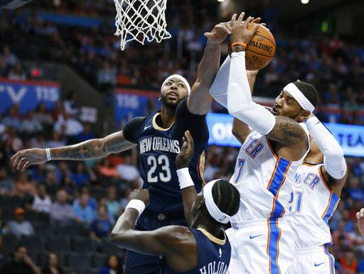 Oklahoma City Thunder forward Carmelo Anthony (7) grabs a rebound in front of New Orleans Pelicans forward Anthony Davis (23) and guard Jrue Holiday during the first quarter of an NBA preseason basketball game in Oklahoma City, Friday, Oct. 6, 2017.
