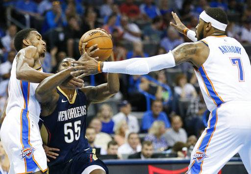 New Orleans Pelicans guard E'Twaun Moore (55) is fouled by Oklahoma City Thunder guard Terrance Ferguson, left, as he drives between Ferguson and forward Carmelo Anthony (7) during the second quarter of an NBA preseason basketball game in Oklahoma City, Friday, Oct. 6, 2017.