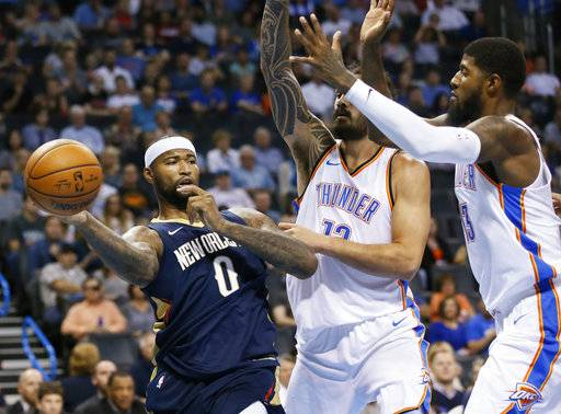 New Orleans Pelicans forward DeMarcus Cousins (0) passes in front of Oklahoma City Thunder center Steven Adams (12) and forward Paul George, right, during the first quarter of an NBA preseason basketball game in Oklahoma City, Friday, Oct. 6, 2017.