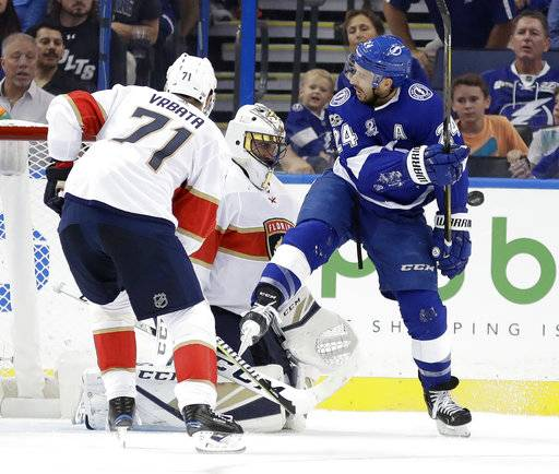 Tampa Bay Lightning right wing Ryan Callahan (24) gets hit with a slap shot in front of Florida Panthers goalie Roberto Luongo and right wing Radim Vrbata (71), of the Czech Republic, during the first period of an NHL hockey game Friday, Oct. 6, 2017, in Tampa, Fla.