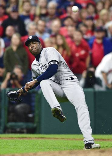 New York Yankees relief pitcher Aroldis Chapman throws to first base to try to get Cleveland Indians' Austin Jackson during the 10th inning of Game 2 of baseball's American League Division Series, Friday, Oct. 6, 2017, in Cleveland. Jackson advanced to second base on a throwing error by Chapman.