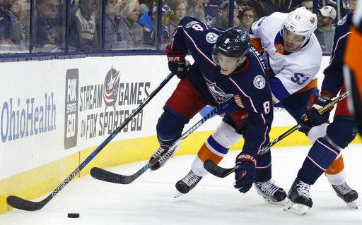 Columbus Blue Jackets' Zach Werenski, left, tries to control the puck as New York Islanders' Casey Cizikas defends during the first period of an NHL hockey game Friday, Oct. 6, 2017, in Columbus, Ohio.