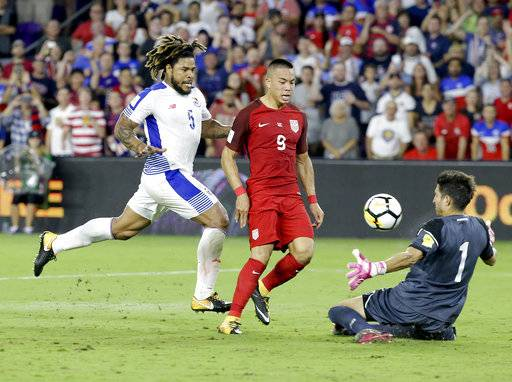 Panama goalkeeper Jaime Penedo (1) blocks a shot by United States' Bobby Wood (9) as Panama's Roman Torres (5) watches during the first half of a World Cup qualifying soccer match, Friday, Oct. 6, 2017, in Orlando, Fla.