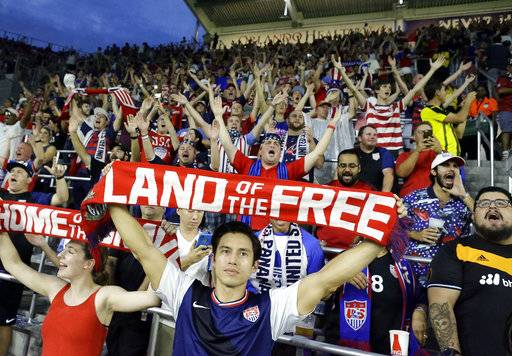 Fans hold banners and cheer as the U.S. team takes the field for a World Cup qualifying soccer match against Panama, Friday, Oct. 6, 2017, in Orlando, Fla. The United States won 4-0.