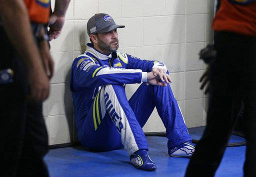 Jimmie Johnson waits as his car goes through inspection before qualifying for Sunday's NASCAR Cup Series auto race at Charlotte Motor Speedway in Concord, N.C., Friday, Oct. 6, 2017.