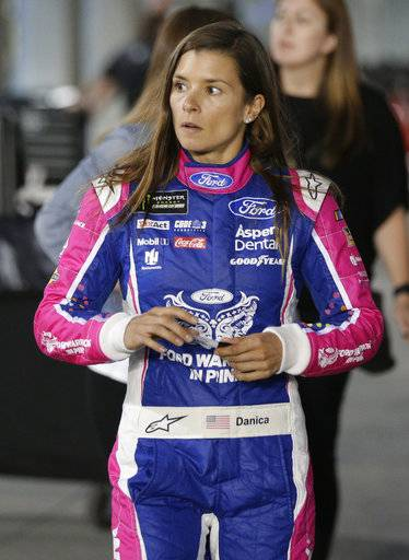 Danica Patrick walks through the garage area before qualifying for Sunday's NASCAR Cup Series auto race at Charlotte Motor Speedway in Concord, N.C., Friday, Oct. 6, 2017.