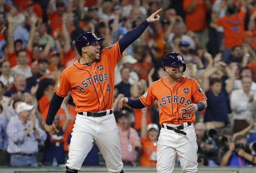 Houston Astros' George Springer (4) and Jose Altuve (27) celebrate after they scored on teammate Carlos Correa's double in Game 2 of baseball's American League Division Series against the Boston Red Sox, Friday, Oct. 6, 2017, in Houston.