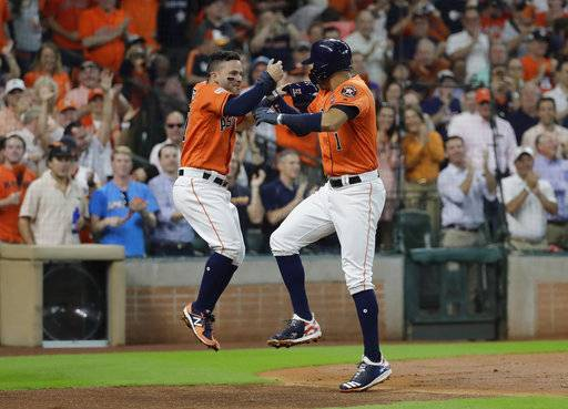 Houston Astros' Carlos Correa, right, celebrates his two-run home run with teammate Jose Altuve, left, during the first inning in Game 2 of baseball's American League Division Series against the Boston Red Sox, Friday, Oct. 6, 2017, in Houston.