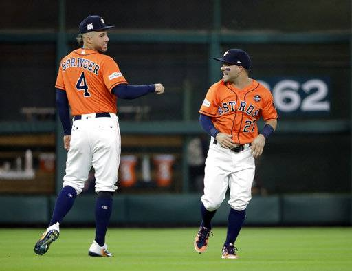 Houston Astros center fielder George Springer (4) and second baseman Jose Altuve (27) prepare for Game 2 of baseball's American League Division Series against the Boston Red Sox, Friday, Oct. 6, 2017, in Houston.
