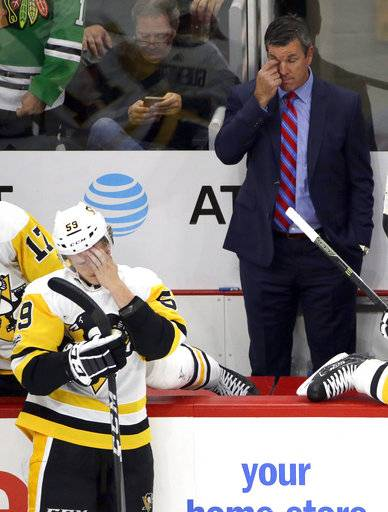Pittsburgh Penguins coach Mike Sullivan, right, and center Jake Guentzel react after Chicago Blackhawks left wing Brandon Saad scored his third goal of the night,p during the third period of an NHL hockey game Thursday, Oct. 5, 2017, in Chicago. The Blackhawks won 10-1.
