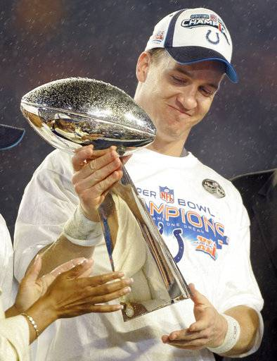FILE - In this Feb. 4, 2007, file photo, Indianapolis Colts' Peyton Manning (18) holds the Vince Lombardi Trophy after the Colts' 29-17 win over the Chicago Bears in the Super Bowl XLI football game at Dolphin Stadium in Miami. At halftime of Sunday's Oct. 8, 2017, game against San Francisco, Manning will become the first player from the franchise's Indianapolis era to have his jersey retired.