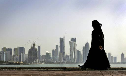 FILE- In this May 14, 2010 file photo, a Qatari woman walks in front of the city skyline in Doha, Qatar. The U.S. military says it has halted some military exercises with Gulf countries over the ongoing diplomatic dispute targeting Qatar.