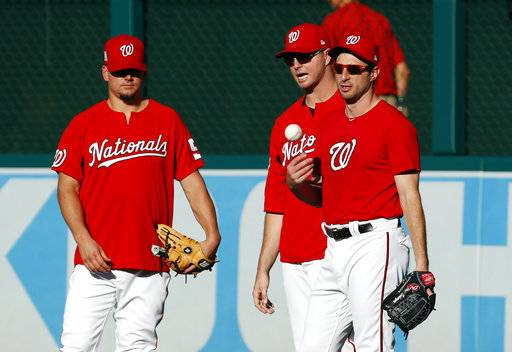 Washington Nationals starting pitcher Max Scherzer, right, tosses a ball as he stands in right field with others during batting practice before Game 1 of baseball's National League Division Series against the Chicago Cubs, at Nationals Park, Friday, Oct. 6, 2017, in Washington.