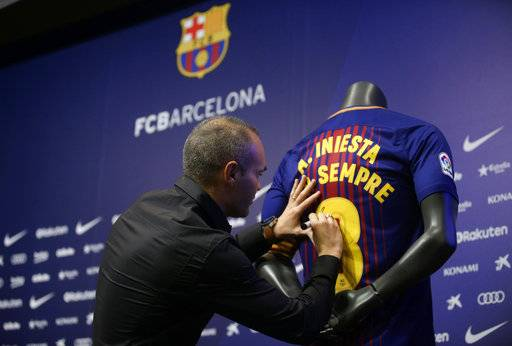 "FC Barcelona's Andres Iniesta signs a shirt reading in Catalan: ""Andres Iniesta forever"" at the Camp Nou stadium in Barcelona, Spain, Friday, Oct. 6, 2017. Barcelona has extended Andres Iniesta's contract ""for life.""."