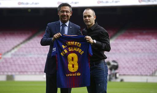 "FC Barcelona's Andres Iniesta, right, and FC Barcelona's president Josep Maria Bartomeu pose with a shirt reading in Catalan: ""Andres Iniesta forvever"" at the Camp Nou stadium in Barcelona, Spain, Friday, Oct. 6, 2017. Barcelona has extended Andres Iniesta's contract ""for life""."