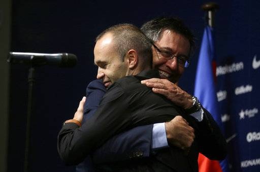 "FC Barcelona's Andres Iniesta, left, hugs FC Barcelona's president Josep Maria Bartomeu at the Camp Nou stadium in Barcelona, Spain, Friday, Oct. 6, 2017. Barcelona has extended Andres Iniesta's contract ""for life.""."