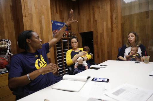 In this Aug. 30, 2017 photo, California women's basketball head coach Lindsay Gottlieb, right, holds her son Jordan while listening to assistant coach Charmin Smith, left, next to fellow assistant Kai Felton, middle, with her son Weston in Berkeley, Calif. The California women's basketball players suddenly have two tiny teammates on board for this season, the new sons of Gottlieb and Felton.