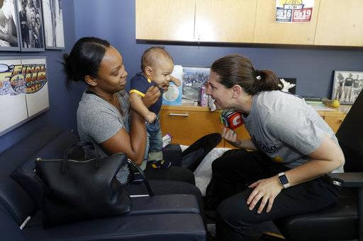 In this Aug. 30, 2017 photo, Jordan Martin, center, is held by his nanny Angelic Lockett, left, as California women's basketball director of basketball Jill Culbertson talks to him in Berkeley, Calif. The California women's basketball players suddenly have two tiny teammates on board for this season, the new sons of head coach Lindsay Gottlieb - Jordan who was born in May - and assistant coach Kai Felton , who gave birth to Weston 10 days early in June.