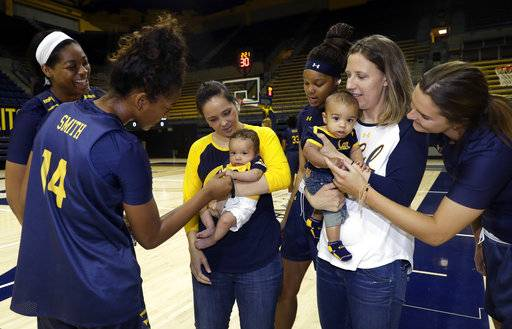 In this Aug. 30, 2017 photo, California women's basketball head coach Lindsay Gottlieb, right, holds her son Jordan next to assistant coach Kai Felton and her son Weston as players surround them in Berkeley, Calif.  The California women's basketball players suddenly have two tiny teammates on board for this season, the new sons of Gottlieb and Felton.