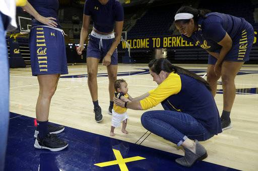 In this Aug. 30, 2017 photo, California women's basketball assistant coach Kai Felton, bottom right, holds her son Weston as players surround them in Berkeley, Calif. The California women's basketball players suddenly have two tiny teammates on board for this season, the new sons of head coach Lindsay Gottlieb - Jordan who was born in May - and Felton, who gave birth to Weston 10 days early in June.