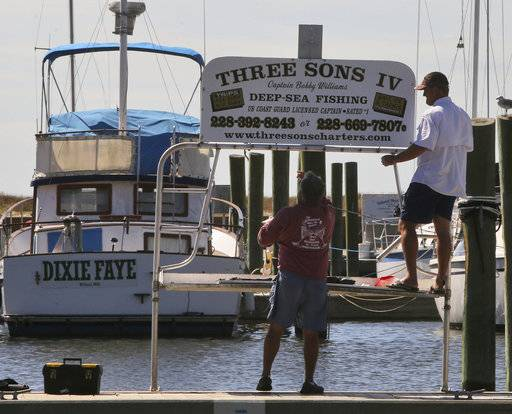 Bobby Williams, left, and his son, Bobby, Jr., take down the sign for their charter boat at the Biloxi, Miss., Small Craft Harbor on Friday, Oct. 6, 2017.  Gulf Coast residents were bracing Friday for a fast-moving blast of wind, heavy rain and rising water as Tropical Storm Nate threatened to reach hurricane strength before a weekend landfall.   (John Fitzhugh/The Sun Herald via AP)