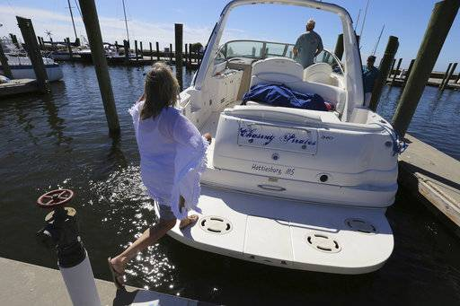 Brenda Kent jumps on her boat as she and her husband leave the Biloxi Small Craft Harbor in Biloxi, Miss., on Friday, Oct. 6, 2017 to take the boat up river in advance of Tropical Storm Nate.  Gulf Coast residents were bracing Friday for a fast-moving blast of wind, heavy rain and rising water as Tropical Storm Nate threatened to reach hurricane strength before a weekend landfall.   (John Fitzhugh/The Sun Herald via AP)