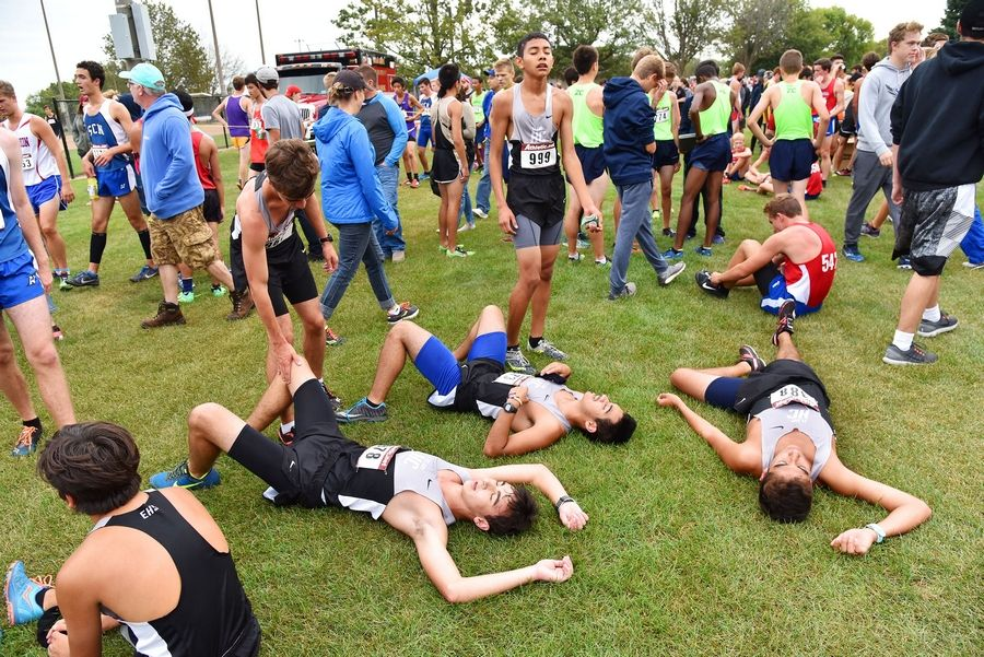 Elgin High School varsity cross country team members lay on the grass at the finish Saturday at the West Aurora Stampede cross country invitational at Stuarts Sports Complex in Aurora.