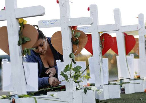 Cece Navarrette places flowers at a cross for her cousin, Bailey Schweitzer, who was among those killed during the mass shooting Friday, Oct. 6, 2017, in Las Vegas. A gunman opened fire on an outdoor music concert on Sunday killing dozens and injuring hundreds.
