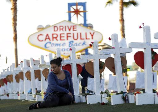 Cece Navarrette sits near a cross for her cousin, Bailey Schweitzer, who was among those killed during the mass shooting Friday, Oct. 6, 2017, in Las Vegas. A gunman, Stephen Paddock, opened fire on an outdoor music concert on Sunday killing dozens and injuring hundreds.