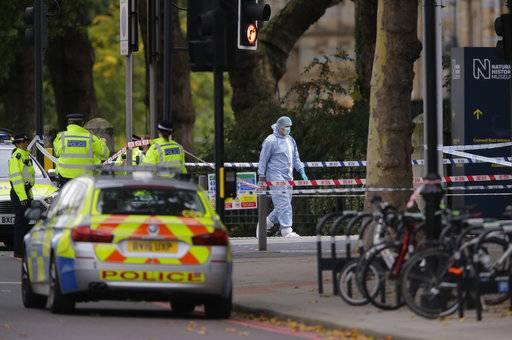 Britain's Police and a forensic investigator at the scene of an incident in central London, Saturday, Oct. 7, 2017. London police say emergency services are outside the Natural History Museum in London after a car struck pedestrians.