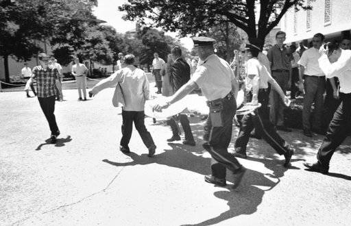 FILE - In this Aug. 1, 1966 file photo, one of the victims of Charles Joseph Whitman, the sniper who gunned down victims from a perch in the University of Texas tower, is carried across the campus to a waiting ambulance in Austin. Survivors of mass shootings say what got them through was leaning on family, friends and counselors.
