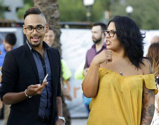 "In this Tuesday, Oct. 3, 2017 photo, Pulse shooting survivor Angel Colon, left, talks with friend Melissa Cruz during a vigil in Orlando, Fla., to show solidarity with the victims of the mass shooting in Las Vegas. Colon was shot six times during the June 2016 massacre at the Pulse nightclub, and says he is still dealing with post-traumatic stress. ""Ambulances, police, even glass, as well, is a trigger. Little specific things, sometimes you forget about, and when you see it, you remember,"" he said. The shooting killed 49 people and injured dozens of others."