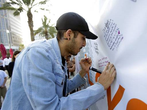 "In this Tuesday, Oct. 3, 2017 photo, Norman Casiano, a survivor of the Pulse nightclub shooting, writes a note on a banner during a vigil in Orlando, Fla., to show solidarity with the victims of the mass shooting in Las Vegas. Casiano was hiding in a bathroom stall with dozens of others when the Orlando gunman shot him twice through the stall door. He's on disability and says he still has anxiety and post-traumatic stress. Las Vegas ""was a big trigger. I still mustered up to come here, and to show the support we were shown last year,"" Casiano said."