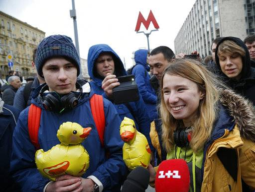 Demonstrators holding yellow ducks are interviewed by journalists as they arrive for a rally in Moscow, Russia, Saturday, Oct. 7, 2017. Opposition leader Alexei Navalny has worked to organize protests in support of his presidential bid across Russia on Saturday, President Vladimir Putin's birthday.