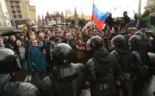 Riot police officers block protesters with Russian flags during a rally in Moscow, Russia, Saturday, Oct. 7, 2017. Opposition leader Alexei Navalny has worked to organize protests in support of his presidential bid across Russia on Saturday, President Vladimir Putin's birthday.