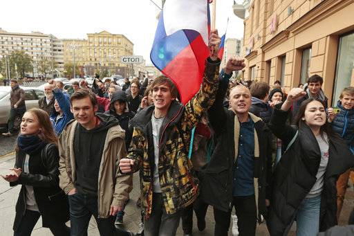 Demonstrators shout slogans and carry the Russian flag during a rally in Moscow, Russia, Saturday, Oct. 7, 2017. Opposition leader Alexei Navalny has worked to organize protests in support of his presidential bid across Russia on Saturday, President Vladimir Putin's birthday.