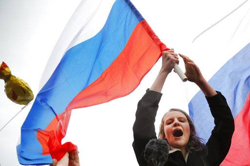 Demonstrators shout slogans and wave Russian flags during a rally in Moscow, Russia, Saturday, Oct. 7, 2017. Opposition leader Alexei Navalny has worked to organize protests in support of his presidential bid across Russia on Saturday, President Vladimir Putin's birthday.