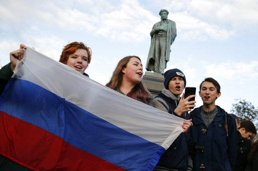 Demonstrators sing as they hold the Russian flag during a rally in Moscow, Russia, Saturday, Oct. 7, 2017. Opposition leader Alexei Navalny has worked to organize protests in support of his presidential bid across Russia on Saturday, President Vladimir Putin's birthday.