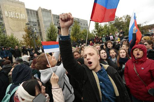 A demonstrator clenches his fist as other hold the Russian flag during a rally in Moscow, Russia, Saturday, Oct. 7, 2017. Opposition leader Alexei Navalny has worked to organize protests in support of his presidential bid across Russia on Saturday, President Vladimir Putin's birthday.