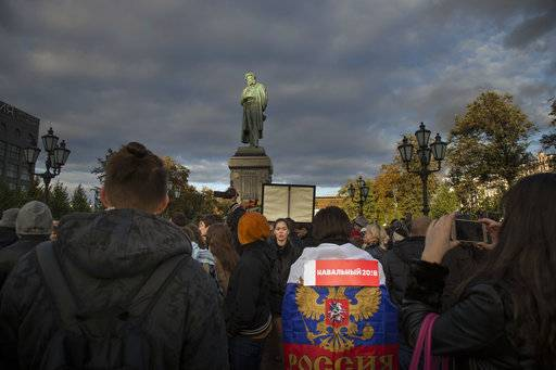 Demonstrators, one of them is draped a Russian national flag over his shoulders gathered during a rally at the statue of Russian poet Alexander Pushkin, background, in Moscow, Russia, Saturday, Oct. 7, 2017. Supporters of opposition leader Alexei Navalny rallied across Russia on Saturday, heeding his call to pressure authorities into letting him enter the presidential race with a wave of demonstrations on President Vladimir Putin's 65th birthday.