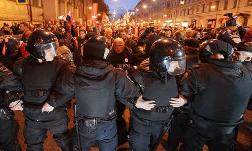 Riot police officers block the way to protesters during a rally in St. Petersburg, Russia, Saturday, Oct. 7, 2017. In a challenge to President Vladimir Putin on his 65th birthday, protesters rallied across Russia on Saturday, heeding opposition leader Alexei Navalny's call to pressure authorities into letting him enter the presidential race.